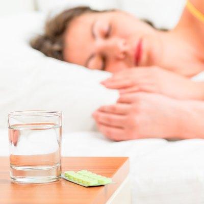 Asleep unhealthy woman and pills on the nightstand