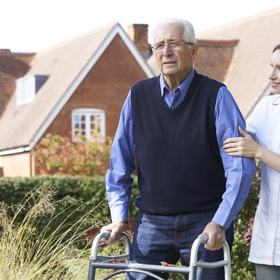 Carer Helping Senior Man To Walk In Garden