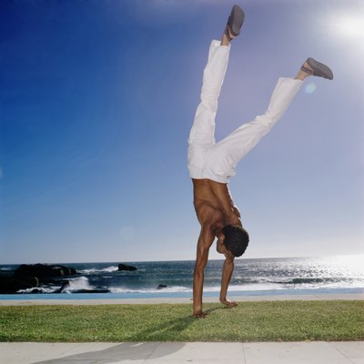 Young man doing a handstand on the grass