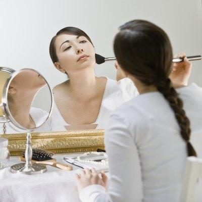 Asian woman applying makeup