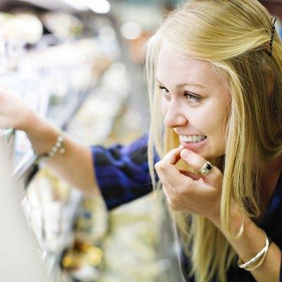Beautiful blonde shopper checks supermarket fridge contents, smiling