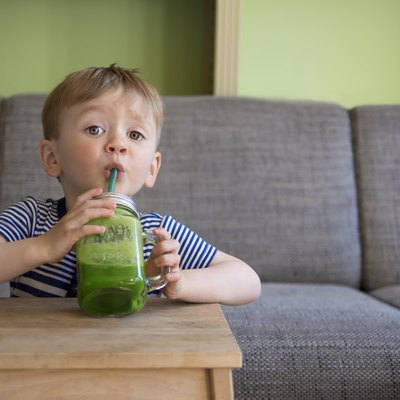 cute child drinking a green smoothie