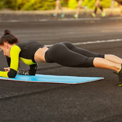 Slim athletic woman doing planking exercise in the stadium, outdoors