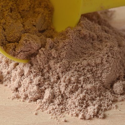 Chocolate protein powder spilled from yellow scoop