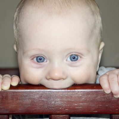 Baby Chewing on Crib