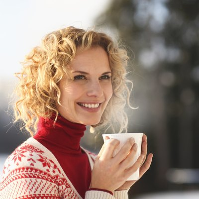 Mid adult woman holding cup outdoors in snow