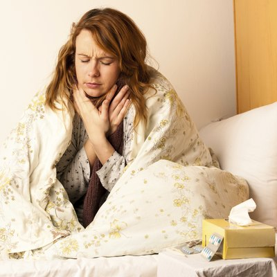 Young woman with sore throat in bed