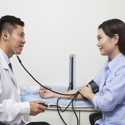 Young Woman Checking Blood Pressure With Male Doctor