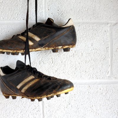 Football boots hang in a changing room
