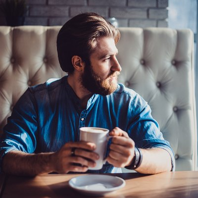 man sitting at cafe with coffee not eating staring out the window