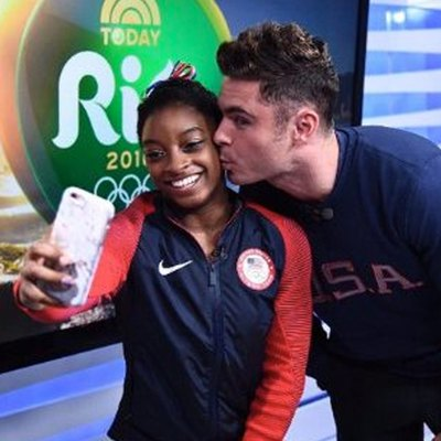 Simone Biles takes a selfie as Zac Efron kisses her cheek