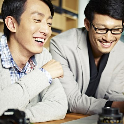 Two co-workers laugh while looking at a laptop.