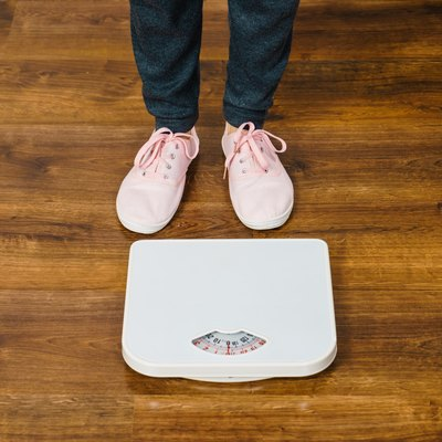 Woman with pink sneakers on bathroom weight scale