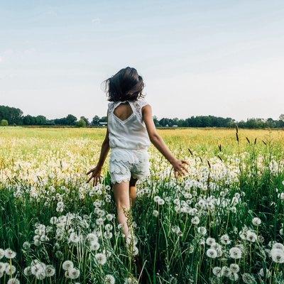 A girl runs through a field.