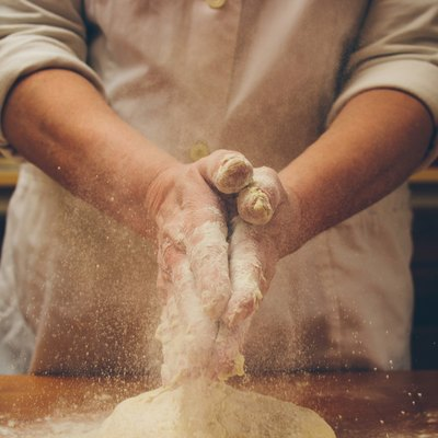 A baker claps some flour from his hands.