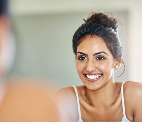 woman looking at healthy skin in mirror