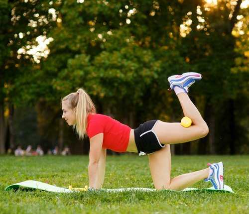 Healthy young sportswoman doing the donkey kick exercise on all fours arching back straightening leg up outdoors. Concept sport, fitness, lifestyle