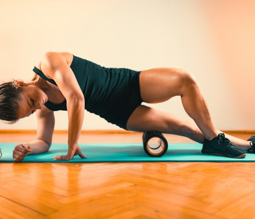 athlete foam rolling a tight it band