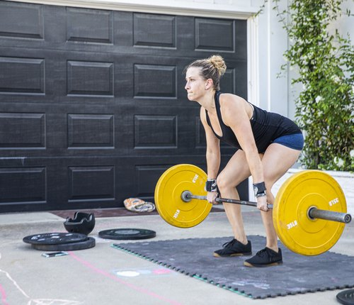 woman doing barbell back exercise in driveway