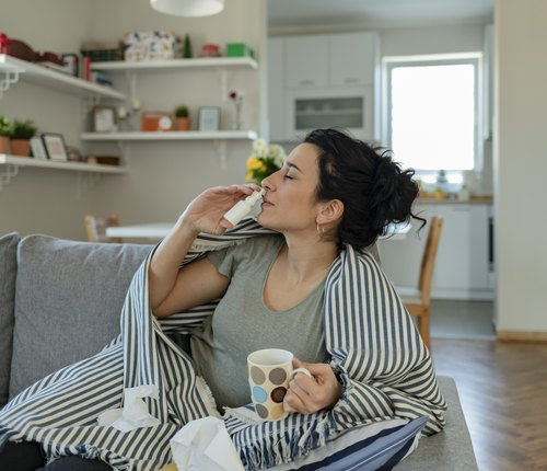 woman trying nasal spray for natural remedy for sinus infection