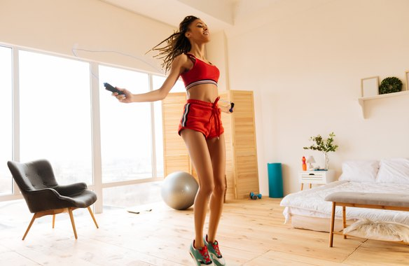 Woman wearing red shorts and top skipping the rope at home