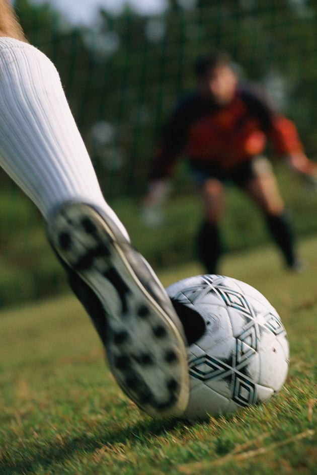Close-up of foot and soccer ball with goalie in background