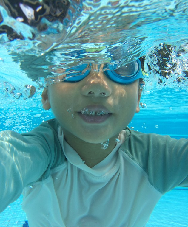 Underwater photo of young asian boy submerged in water