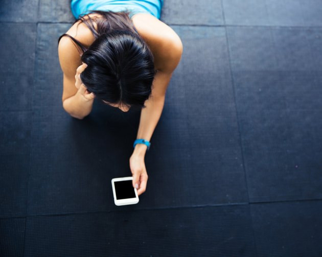 Woman lying on the floor with smartphone
