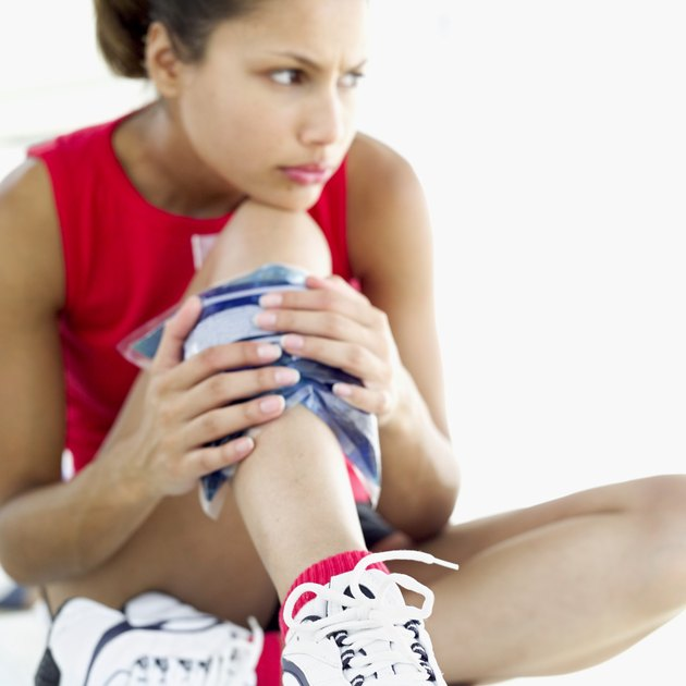 woman applying a cold pack to her leg