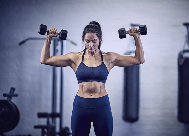 Woman doing dumbbell overhead press for the best shoulder workout