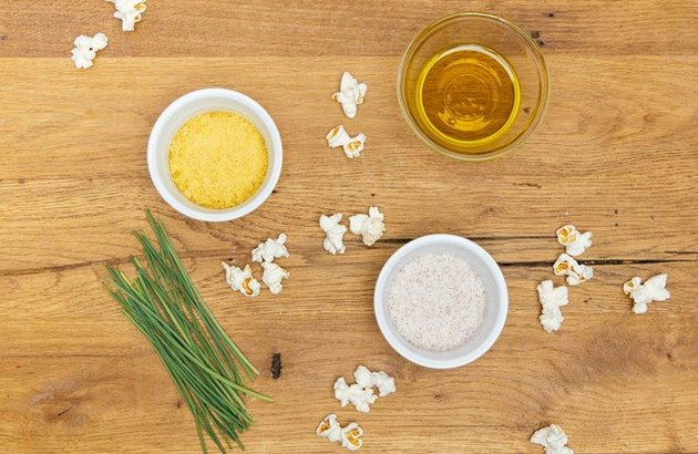 Popcorn on wooden table with nutritional yeast and chives