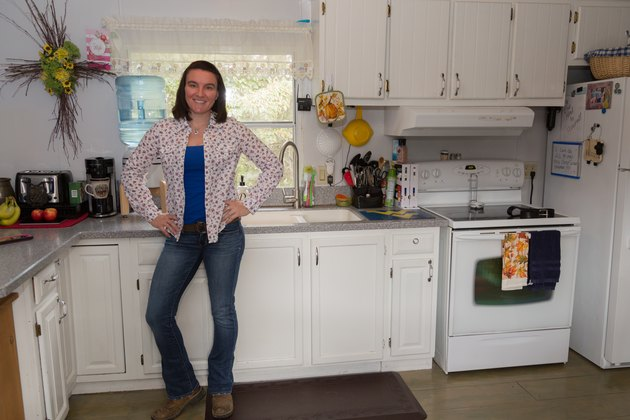 Brittany stands in her kitchen.