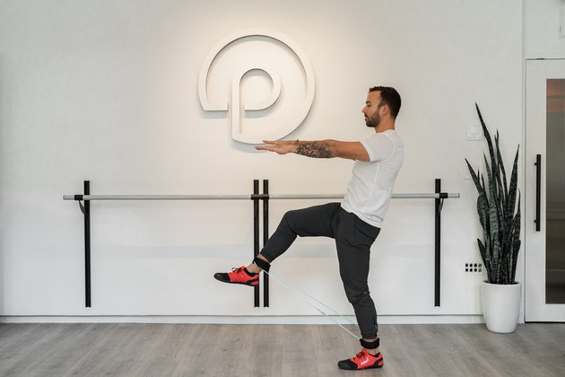Man Doing Standing Forward Toe Tap and Squeeze With Resistance Band