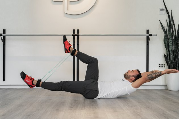 Man Doing Hollow Body Alternating Leg Squeeze With Resistance Band