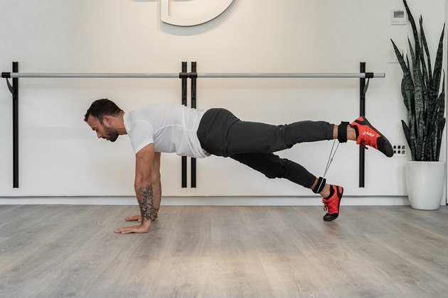 Man Doing Plank + Wide Straight Leg Raise With Resistance Band