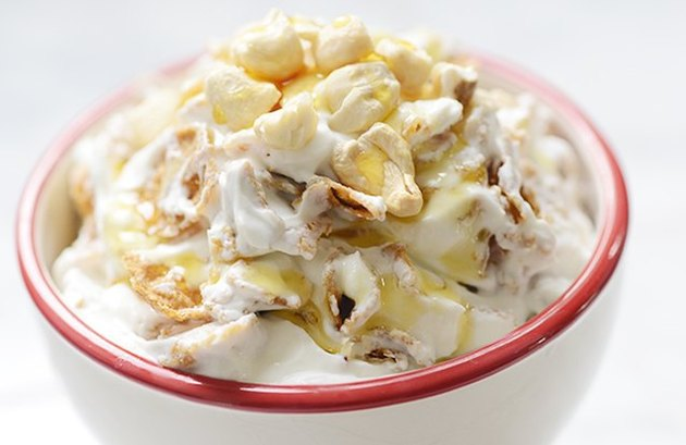 A bowl of yogurt topped with cashews and maple syrup