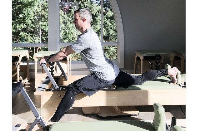 man performing pilates split on reformer