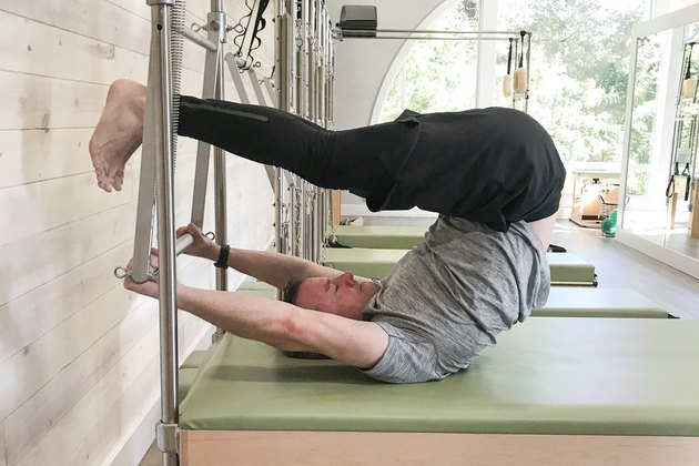 man performing overhead pilates exercise