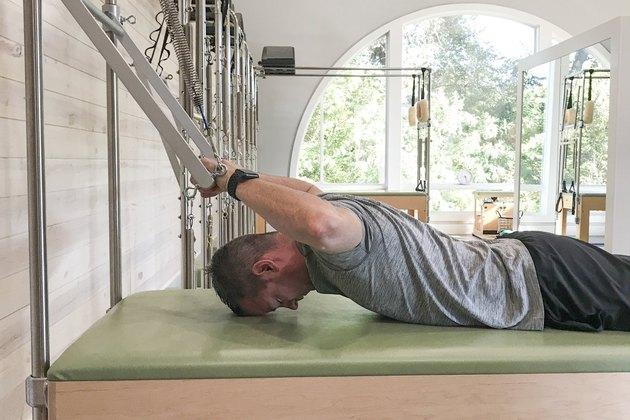 man doing babby bird pilates movement