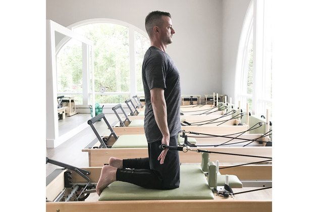 man performing chest expansion pilates exercise
