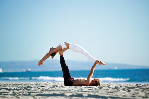 Acroyoga couple on the beach with woman performing back extension.