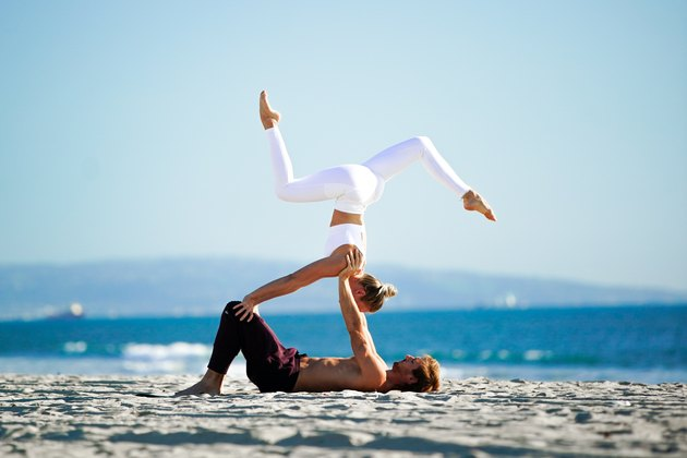 Woman performing headstand variation with yoga partner on the beach.