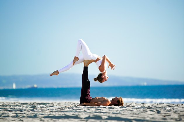 Woman performing a backbend on her yoga partner's feet on the beach.
