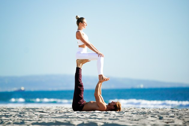 Woman sitting upright on partner's feet in an acroyoga pose on the beach.