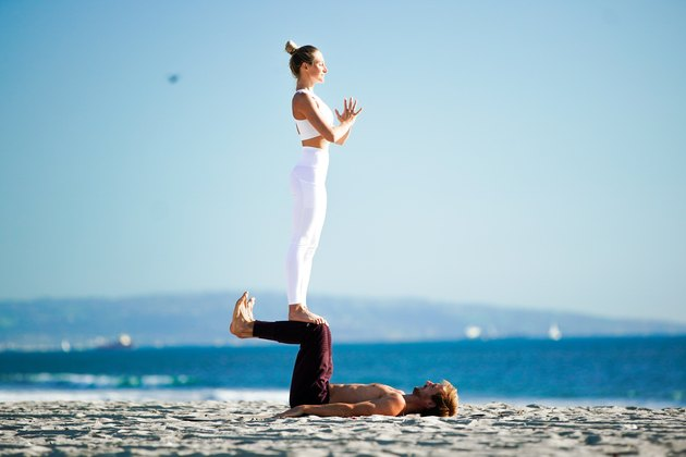 Woman standing on partner's shins on the beach.