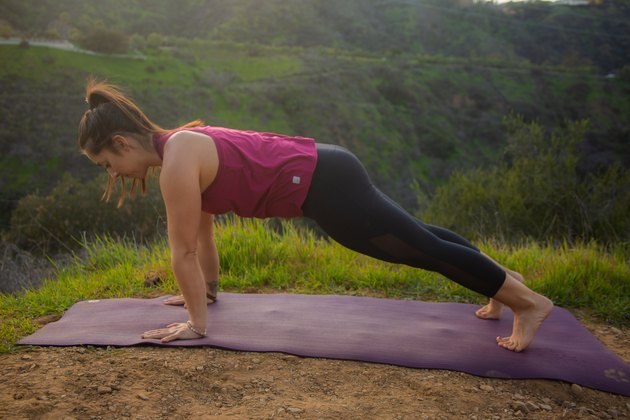 Woman performing plank pose on a yoga mat.
