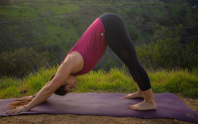 Woman performing downward facing dog yoga pose.