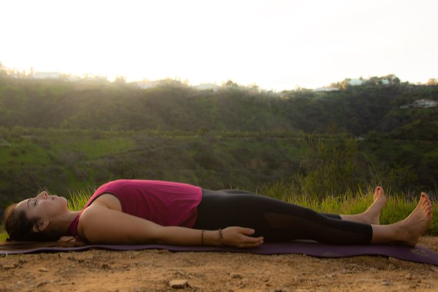 Woman relaxing on her back on yoga mat.