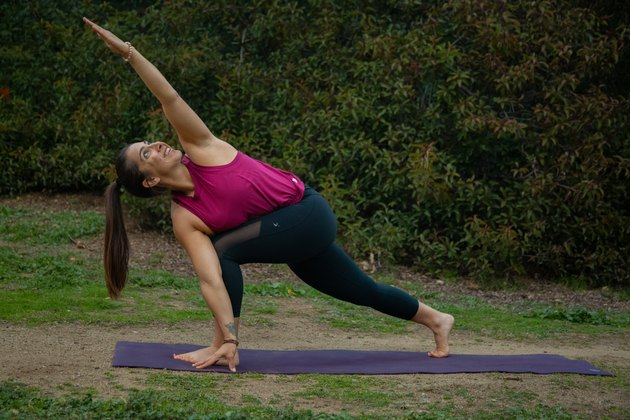 Woman performing yoga pose outdoors.
