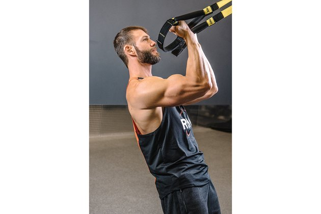 Man demonstrating how to do TRX Biceps Curls